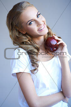 Head shot of woman holding red apple against grey