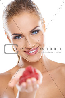 Close up of smiling blonde holding raspberries