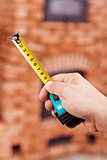 Construction worker hand with tape-measure