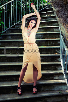 Beautiful young woman in a garden stairs.