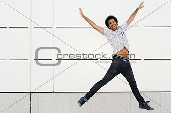 Man with curly hairstyle jumping in urban background