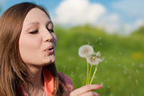 Young beautiful woman blowing on dandelion flower