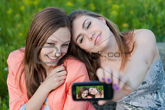 Two happy teenage girl friends and mobile