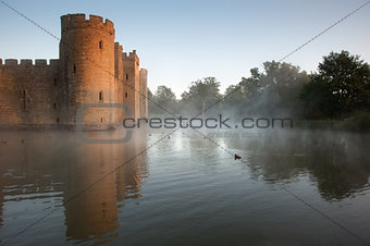 Stunning moat and castle in Autumn Fall sunrise with mist 