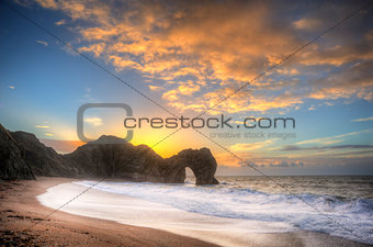Vibrant sunrise over ocean with rock stack in foreground