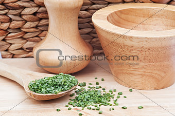 Chopped chives in rustic kitchen setting with wooden pestle and