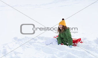 Girl with sleigh sitting in snow