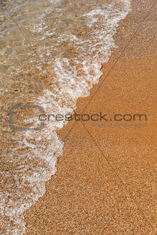 sea €‹caresses the sand on the beach