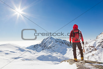 Mountaineer looking at a snowy mountain landscape