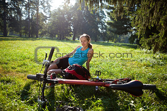 Young girl cyclist with bike relaxation in spring park