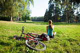 Girl cyclist relax front view panorama of the spring park