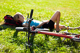 Young girl cyclist enjoying relaxation lying in the fresh green 