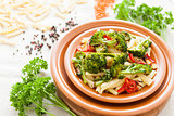 Delicious pasta with roasted vegetables on a plate closeup