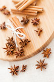 Pile of cinnamon sticks and anise on a wooden board close up