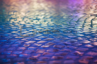 Cobble Stone Pavement - Reflexion in Urban Night. Wet Blue Sidewalk