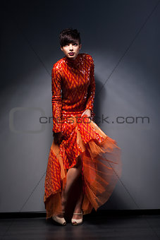 Trendy Brunette posing in Red Dress. Studio Shot