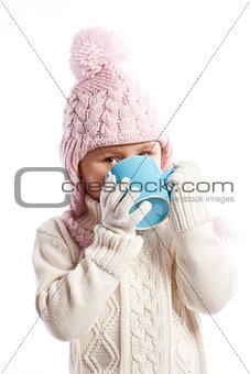 Little girl drinking hot beverage.
