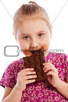 Young girl eating a chocolate bar.