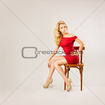Sexy Blonde Woman in Red Fashion Dress Sitting on a Chair