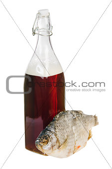 A bottle of domestic beer and dried fish is isolated on white