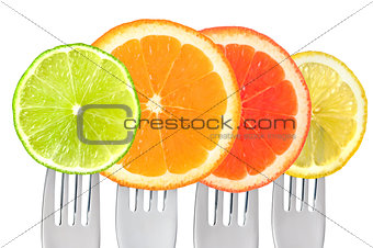 citrus fruit on forks isolated on white