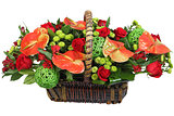 Red-and-green floral arrangement in a wicker basket.