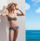blonde girl in bikini near the wall with hat