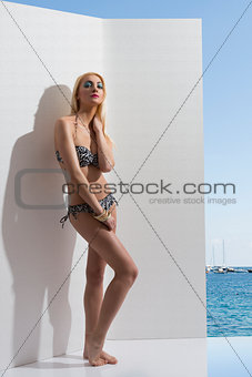 blonde girl in bikini near the wall with hand near the neck