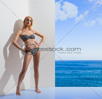blonde girl in bikini near the wall with hands on the hips