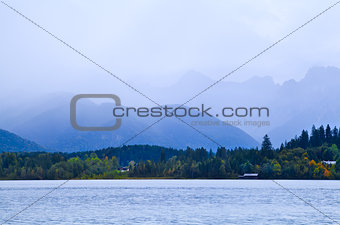 mountains in fog by lake