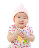 Asian baby girl gripping a toy