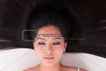 Asian girl lying on white with scatter hair