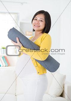 Asian pregnant woman holding yoga mat