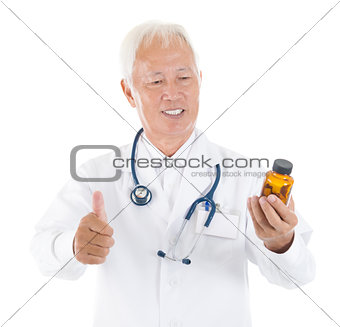 Asian senior medical doctor holding a bottle of pills