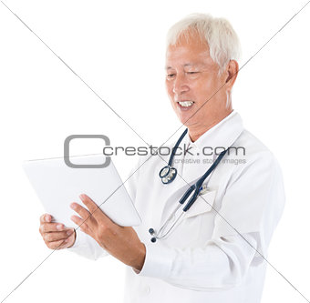 Asian specialist medical doctor using tablet computer