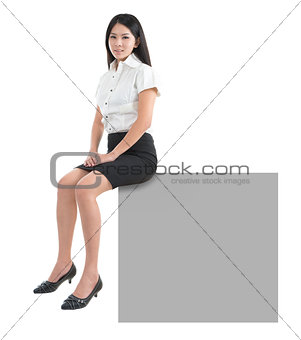 Asian girl sitting on blank billboard