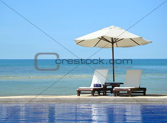 Two chairs and white umbrella on the beach