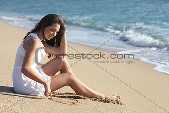 Beautiful woman drawing a heart in the sand