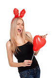 Young woman winking with balloon in hands