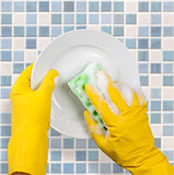 Hands in yellow gloves washing dish on tile kitchen background