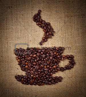 coffee cup made from beans on burlap background