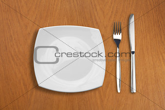 square white plate, knife and fork on wooden table