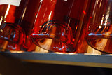 Close-up of bottom of red wine bottle on rack.