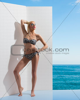 blonde girl in bikini near the wall with closed eyes