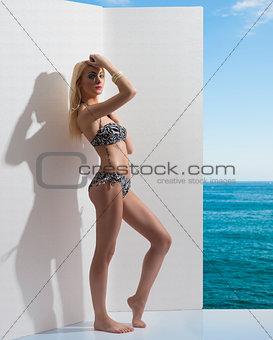 blonde girl in bikini near the wall with hand on the head