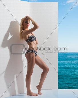blonde girl in bikini near the wall with hand on the head