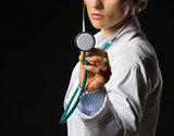 Closeup on medical doctor woman using stethoscope isolated on bl