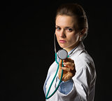 Confident medical doctor woman using stethoscope isolated on bla