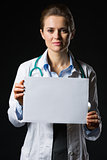 Medical doctor woman showing blank billboard isolated on black
