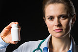 Medical doctor woman showing medicine bottle on black background
